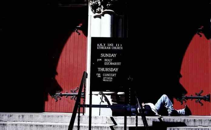 Photographed on small-format film, Kodak's Gold ULTRAMAX, 400 speed. I realized an individual sleep on a church's front steps in Manhattan, across from Central Park. The red doors came after noticing his sleep or resting at this particular location. The light look like wings to me and the distance allowed me to use a big aperture setting without going to a small aperture setting just for clear details. The gritty film texture of the door, natural light and 400 speed came into together very well, visually.
