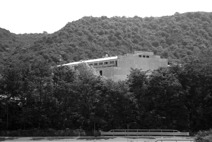 """A view from the LRF of the former industrial coater building (""""Big Boy""""), now empty and partially demolished and idling behind the lush trees in the valley carved by the Fiume Bormida - FILM FERRANIA P30, June 2017"""