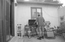 Untitled - A man barbecues in his backyard porch on Independence Day Weekend, Broomfield CO, July 2017 (Nikon F100, 20mm, ILFORD HP5 Plus) - Kenneth Wajda Photographer