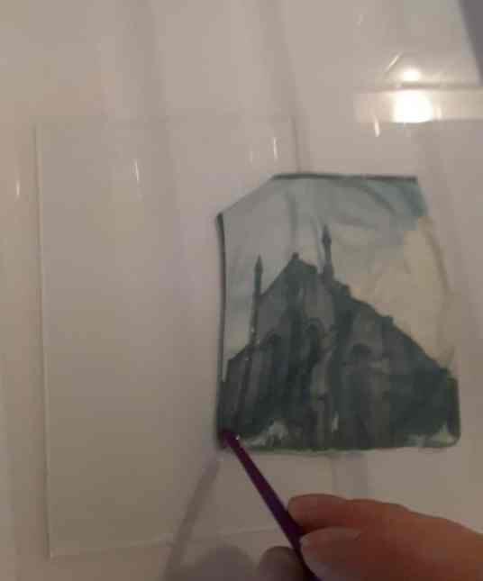 Tutorial step 2: using the rear of a paintbrush to guide the emulsion onto a glass plate.