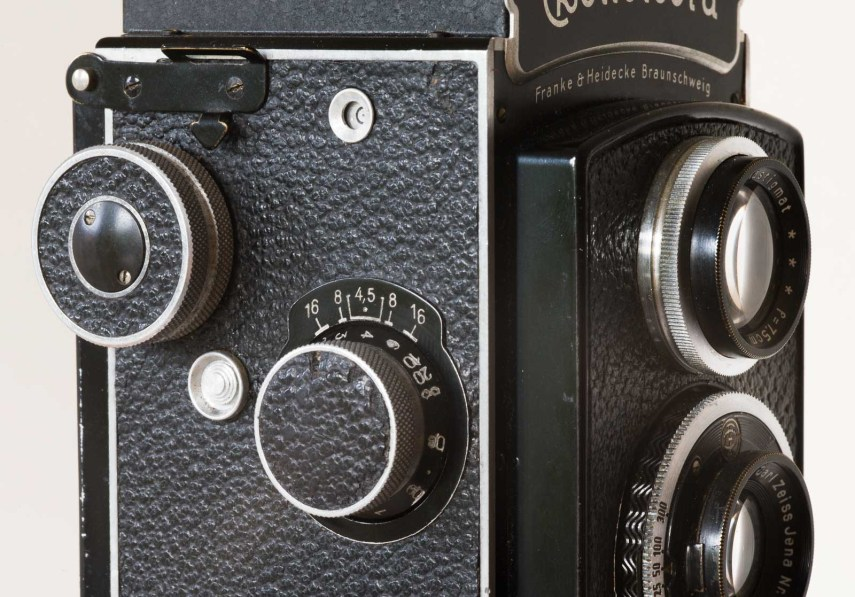 Rolleicord side view showing film winding knob, frame number window, reset button and focusing knob with DOF markings