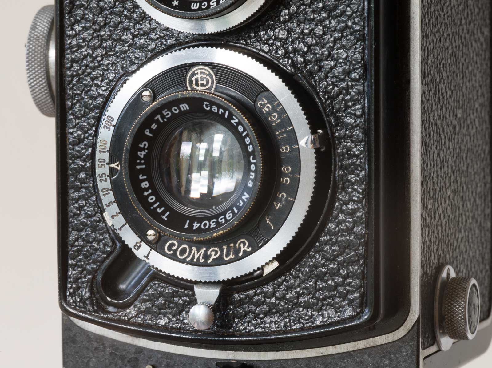Rolleicord taking lens in Compur shutter with tensioning and release lever at bottom