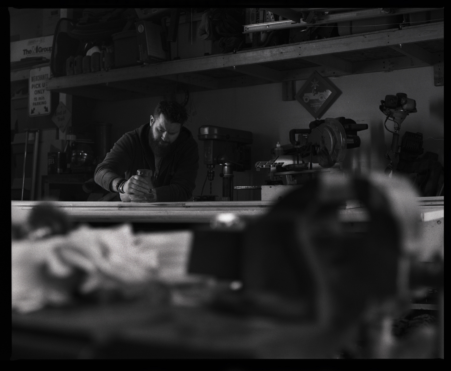 Woodworker - ILFORD HP5 PLUS. I wanted a dirty foreground to bury Simon in his work. I loved the way his busy workshop framed him within his task at hand.