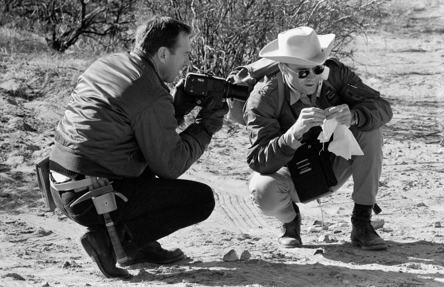 Back-up Commander Jim Lovell (left) looking on and holding a Hasselblad, Back-up Lunar Module Pilot Fred Haise (right) examines a sample during the Sierra Blanca trip (NASA: AP11-S69-25199)