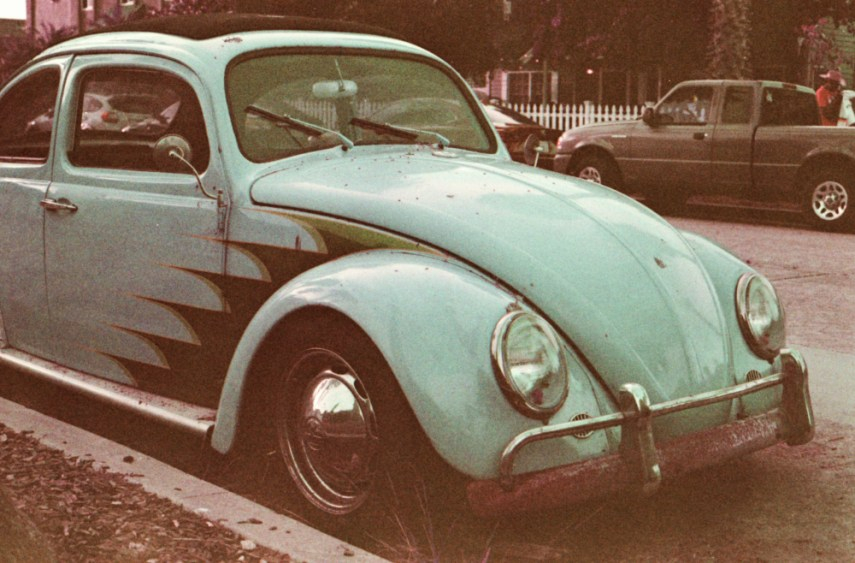 a green vw beetle parked at the side of the road