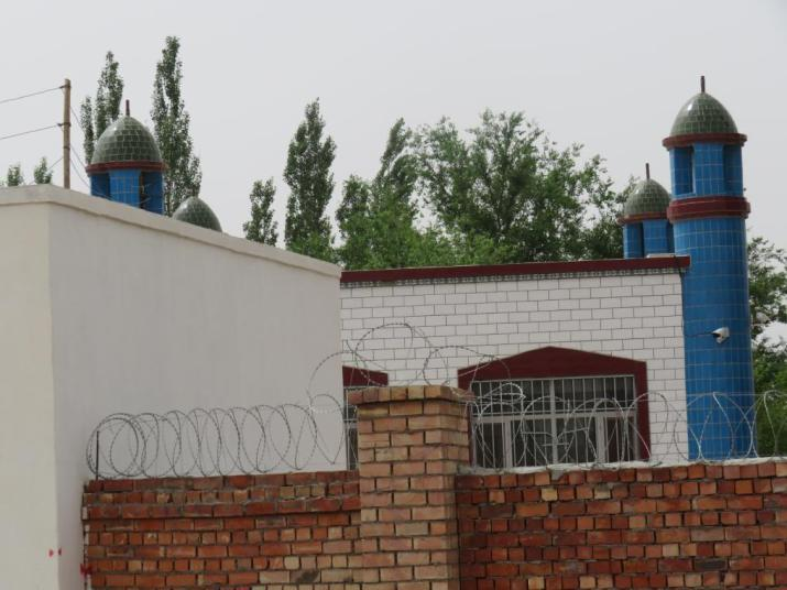 The crescent has been removed from the top of the Juma mosque in Shang Village's No. 3 Production Team. Surveillance cameras on the mosque and razor wire on its wall are clearly visible.