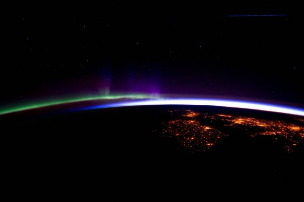 ng at an altitude of about 240 miles over the eastern North Atlantic, the Expedition 30 crew aboard the International Space Station photographed this nighttime scene. This view looks northeastward. Center point coordinates are 46.8 degrees north latitude and 14.3 degrees west longitude. The night lights of the cities of Ireland, in the foreground, and the United Kingdom, in the back and to the right, are contrasted by the bright sunrise in the background. The greens and purples of the Aurora Borealis are seen along the rest of the horizon. This image was taken on March 28, 2012.