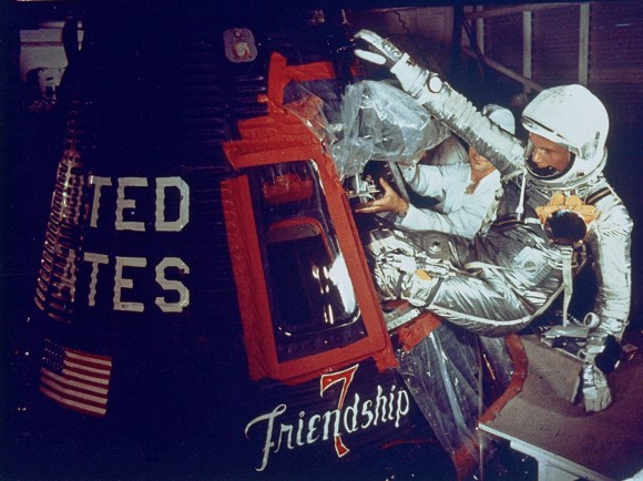Man in silver suit writhing feet first into small space capsule.