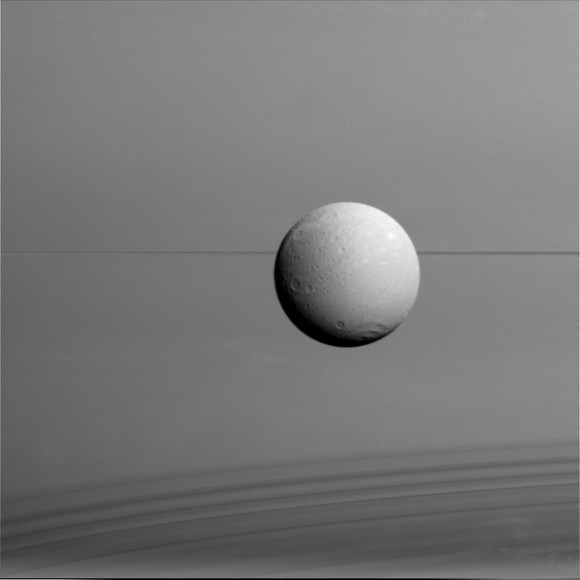 Dione hangs in front of Saturn and its icy rings in this view, captured during Cassini's final close flyby of the icy moon. Image credit: NASA/JPL-Caltech/Space Science Institute