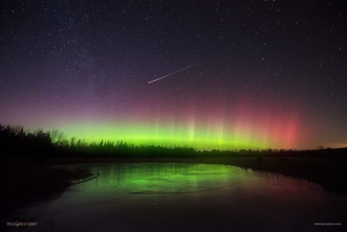 The green glow of the northern lights on the horizon with a bright meteor above it.