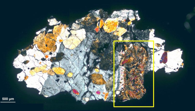 Irregular colored blotches like crystals in a cut section of a rock.