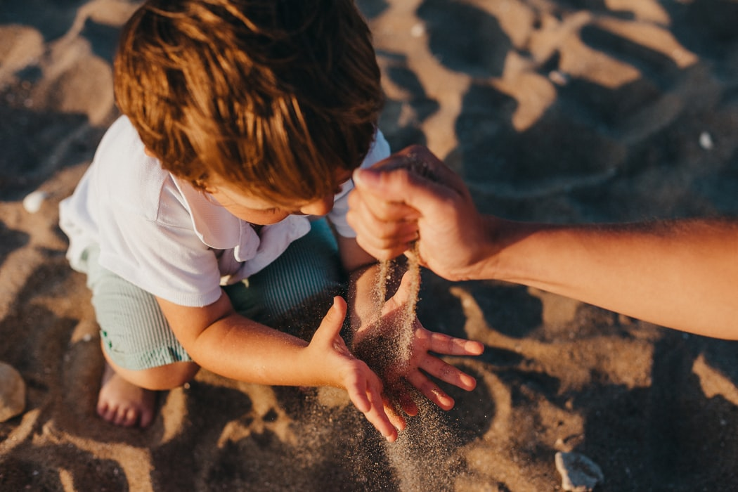 father and son playing with sand