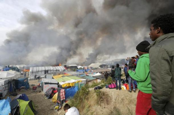 """Migrants look at burning makeshift shelters and tents in the """"Jungle"""" on the third day of their evacuation as part of the dismantlement of the camp called the """"Jungle"""" in Calais"""