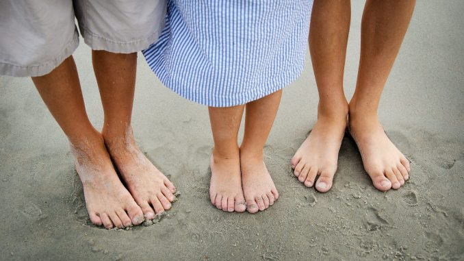 Photo of three pairs of feet standing in the sands of a beach