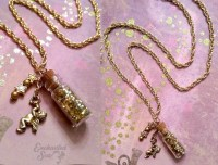 Shimmering gold beads and a musical cherub dangle from a bottle of iridescent gold magical dust.