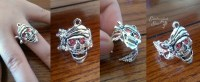 A grinning pirate skull with two ruby-colored gemstone eyes adorns a delicate silver filigree ring.