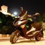 Imagen de la Kyoto Edison, tomada de noche, con la moto aparcada y de fondo la Alhambra iluminada.