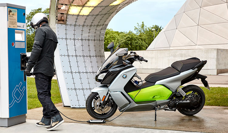Imagen donde vemos el maxiscooter BMW C Evolution recargando su baterías en un punto de recarga.