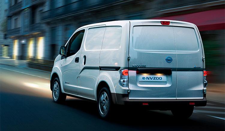 imagen trasera de la furgoneta eléctrica Nissan e-NV200 circulando de noche por una ciudad.