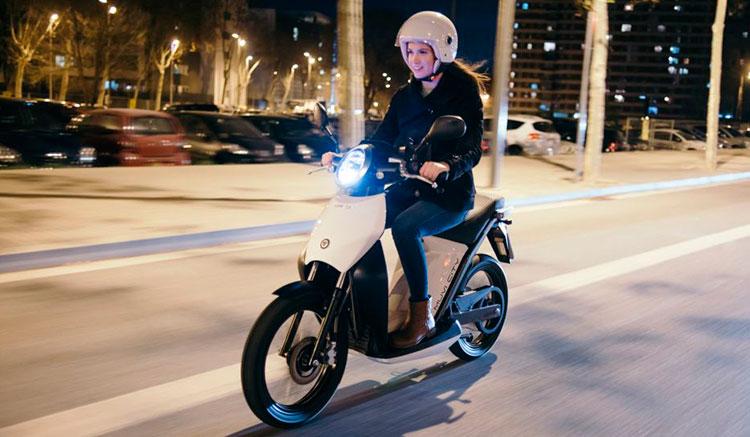 Imagen donde vemos una chica conduciendo la Torrot Muvi, de noche por ciudad.