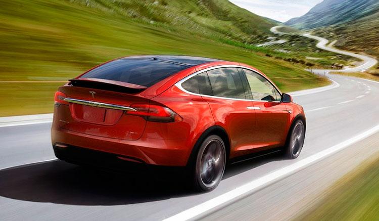 Imagen donde podemos ver un Tesla Model X circulando por una carretera de curvas. En esta vista trasera podemos apreciar el diseño de la zona trasera del vehículo.