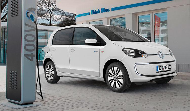 Imahen donde vemos un Volkswagen e-Up, recargando sus baterías en una toma de conexión para coches eléctricos.