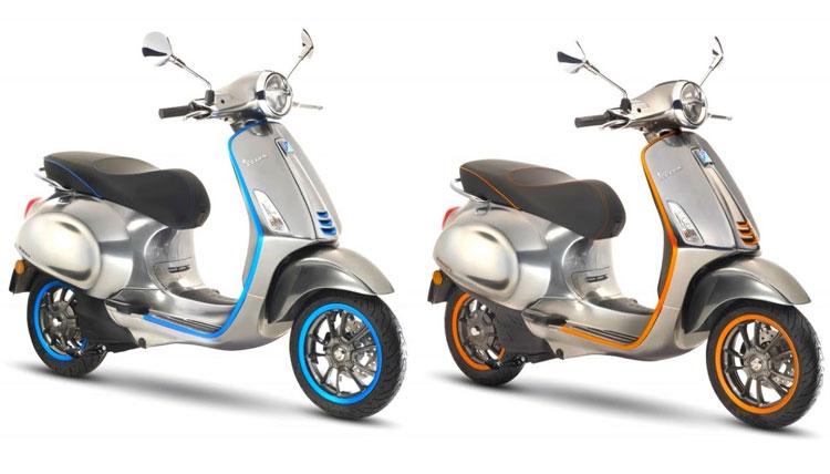 Imagen donde podemos ver dos Vespa Elettrica, una de color azul y otra de color naranja.