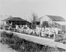A Fairbanks, Alaska, party c. 1918. Note the raised wooden sidewalk and the greenhouse attached to the house. Fairbanks had only been founded in 1901. Photo by National Photo Company.