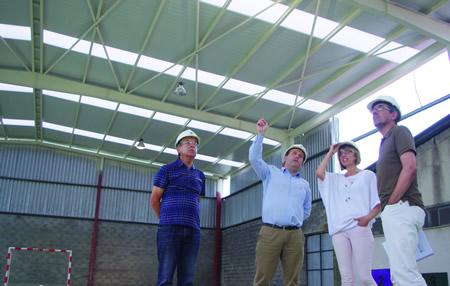 Raquel Arias e Luis Fernández Guitián escoitan as explicacións dos técnicos a cargo das obras da cuberta do polideportivo do CEIP de Sober.  GPDL.