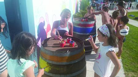 Nenos e nenas decoran barricas durante o curso de pintura que se desenvolve nas Piscinas de Sober. (Foto cedida).