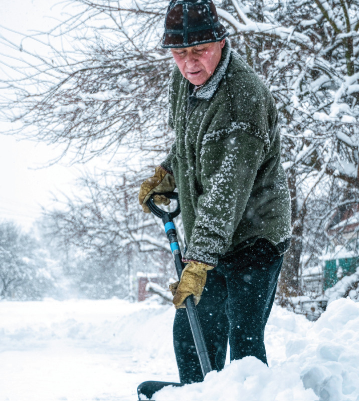 Senior man shoveling in a blizzard