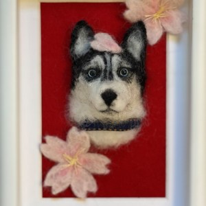 Framed, needle-felted portrait of a husky with 2 pink-and-white flowers in the corners and a flower petal on the huskey's head. The background of the portrait is red and the frame is white. The huskey has blue eyes.