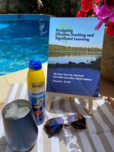 The book Designing Effective Teaching and Significant Learning with sunscreen and sunglasses next to a pool.