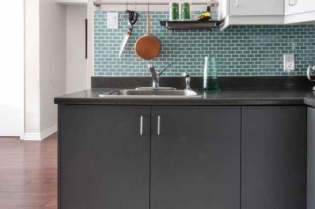Small Kitchen with green grey cupboards and a green brick pattern splash back