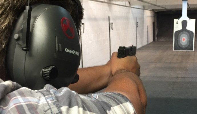 Man with a firearm aiming at target