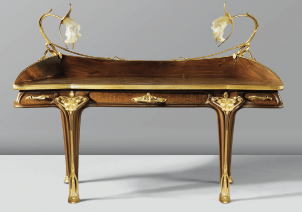 A mahogany desk with inlaid veneers, gilt bronze mounts, and leather writing surface. Designed by Louis Majorelle