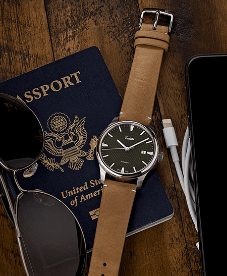 Swiss-made watch featuring a green dial and Eta 2824-2 automatic movement with a genuine leather strap set beside passport and sunglasses