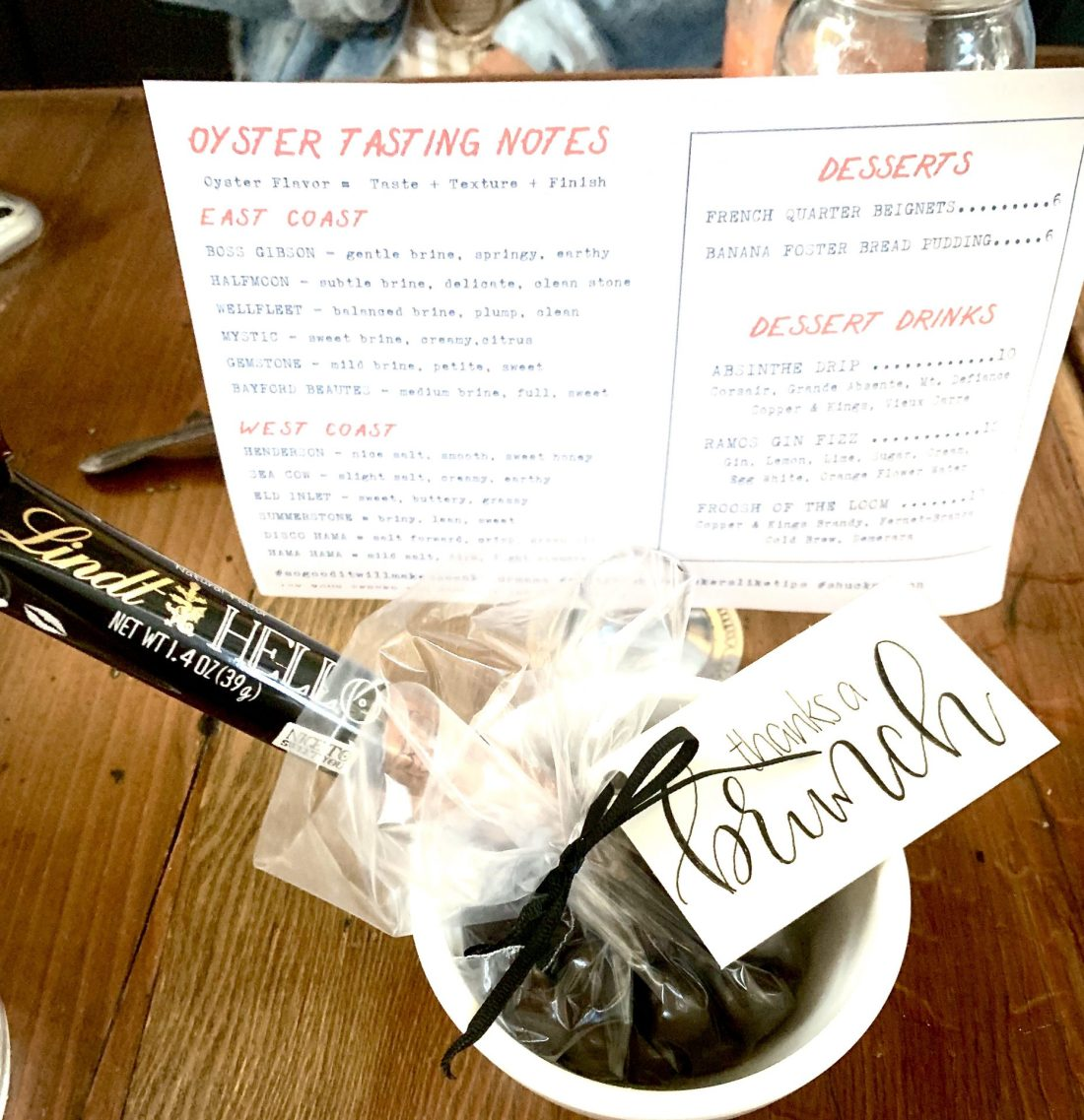 Brunch gift including a Lindt chocolate in front of an oyster menu
