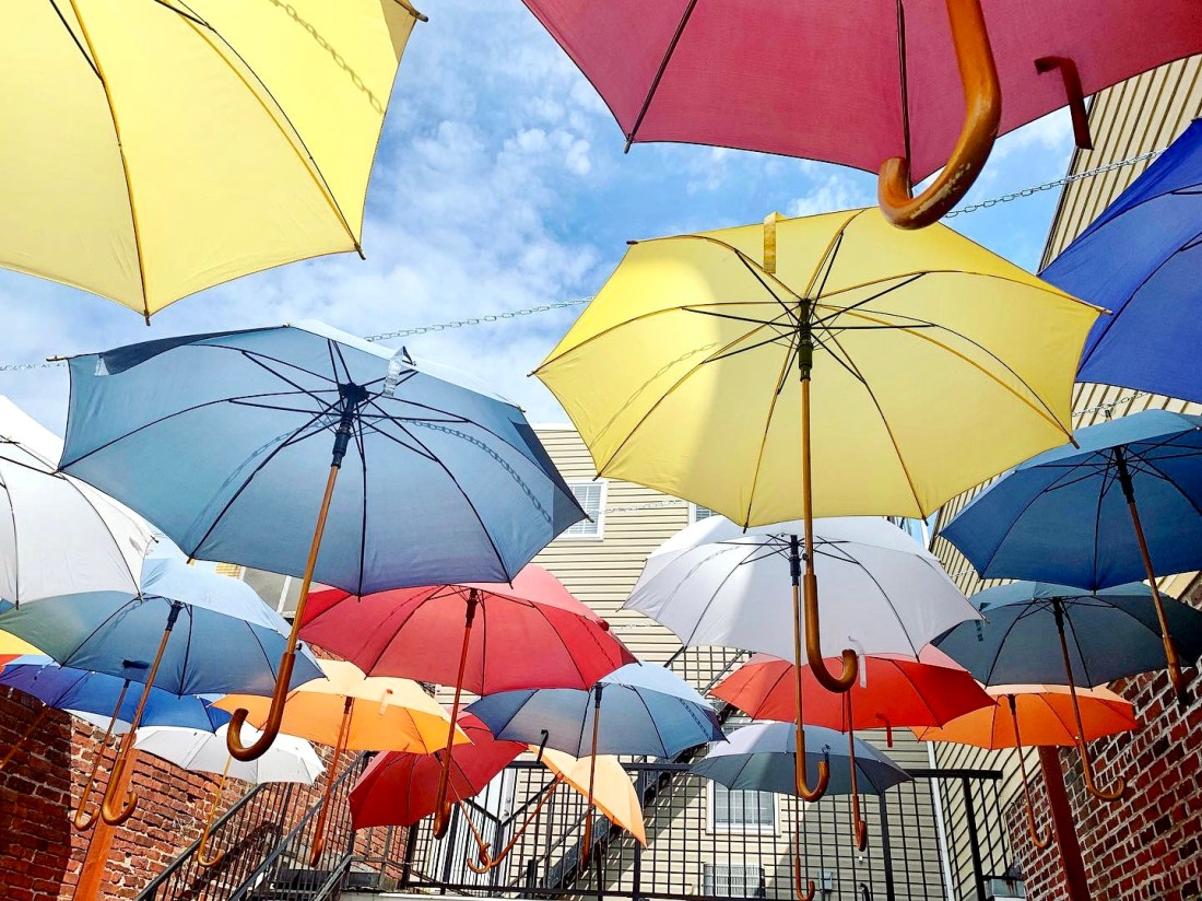 Rainbow umbrellas cover the outdoor patio at Caffe Mona