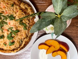 Langostino Alfredo Pasta Dutch Baby Pancake with a side of peaches