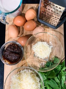 All of the ingredients for the crustless french onion quiche from the bottom left there's a cup of shredded asiago, two handfuls of spinach, half a cup of french onion spread, parmesan, six organic brown eggs, one cup of almond milk, and a cheese grater
