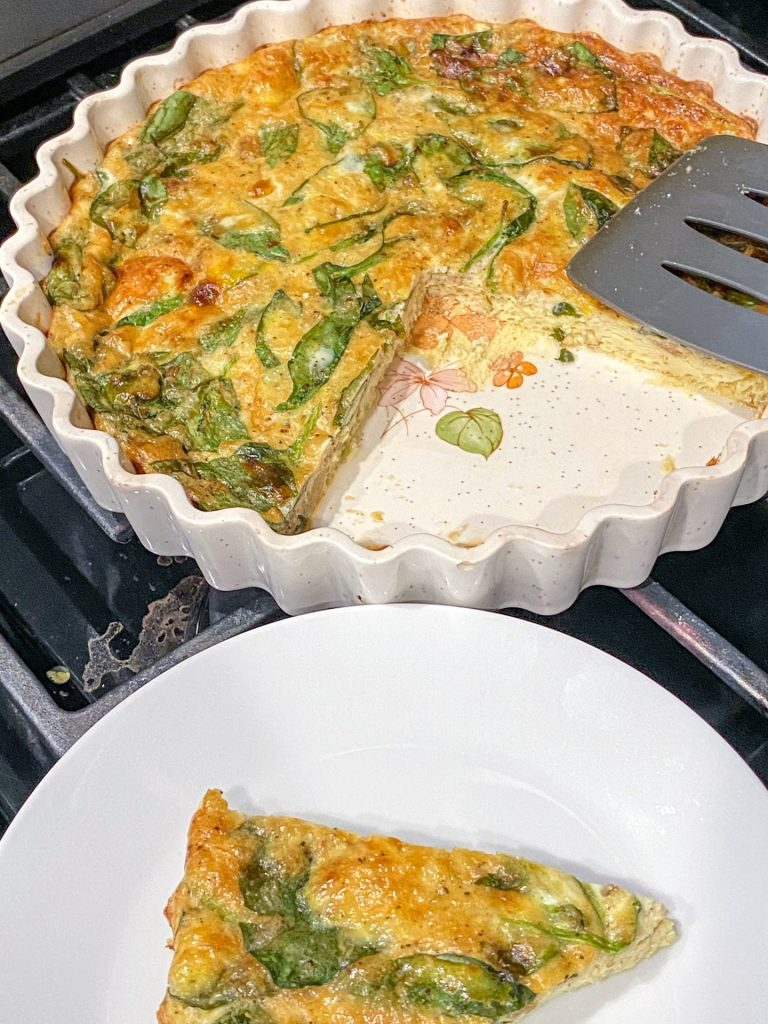 A slice of the crustless quiche that's made with asiago, spinach, and french onion spread is plated and ready to be served for brunch next to the rest of the quiche.