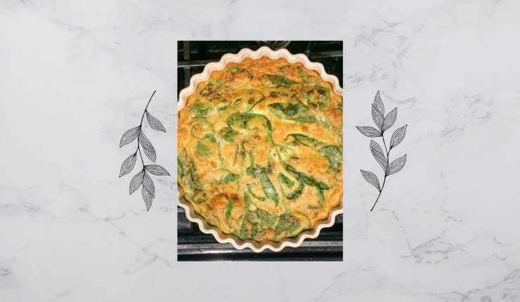 Crustless french onion and spinach quiche right out of the oven and ready for brunch. A marbled background with stencil plant drawings are on the side of the quiche.