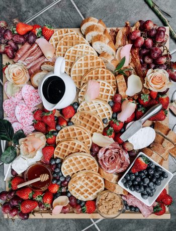 Brunch board with waffles, cheese, samami roses. seasonal fruit, honey, maple syrup, and peanut butter for a romantic brunch at home.