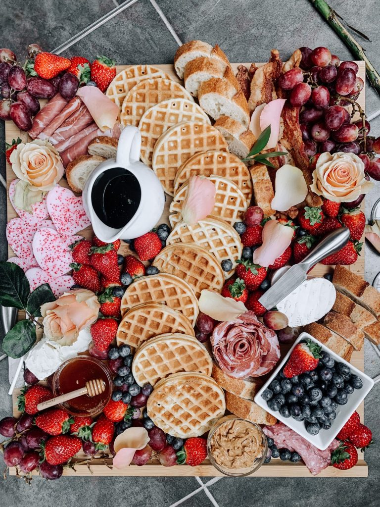 A Brunch Board with waffles, cheese, fruit, honey, peanut butter, toast, salami roses, and decorative flowers.