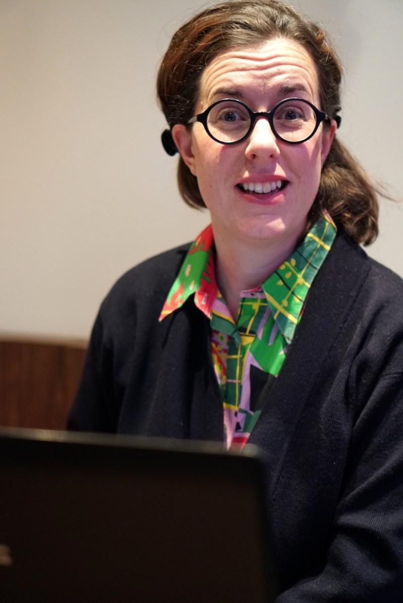 emilia sitter vid dator i färgglad skjorta, svarta glasögon