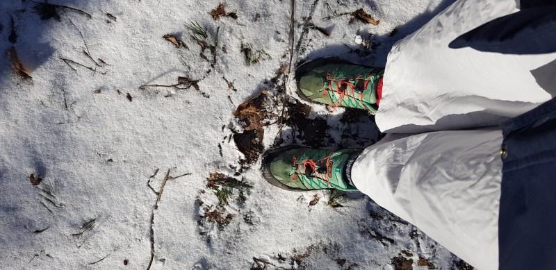 Ute i naturen är att leva billigt. Gröna skor och vita byxor på snötäckt mark