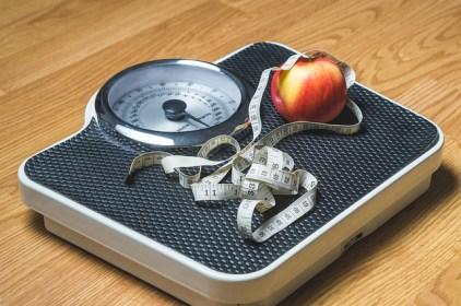 une balance et une pomme : le jeûne intermittent permet de perdre du poids en mangeant