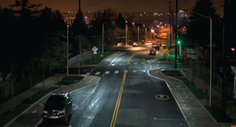 Photo of a road at night with streetlights on either side.