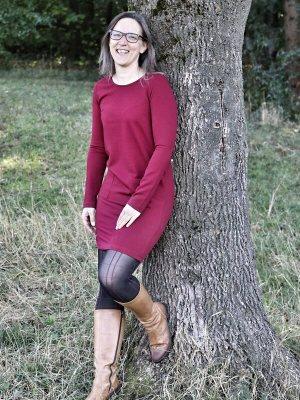 Junge Frau lehnt an einem Baum und lacht in die Kamera. Bild als Dekoelement Tierkommunikation nicht nur für Tiere